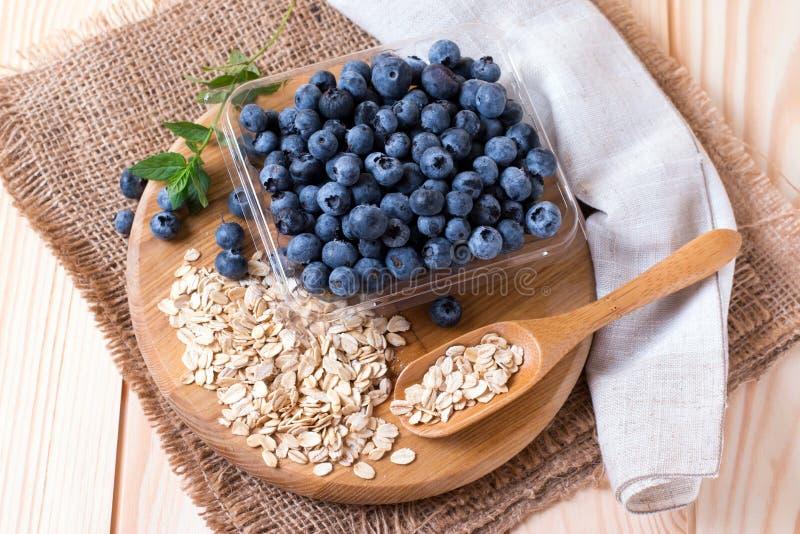 未加工的燕麦粥用在委员会的新鲜的蓝莓 免版税库存照片