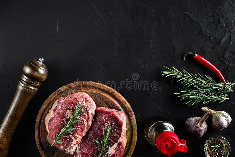 未加工的牛排用香料和成份烹调的在切板和板岩背景 顶视图 免版税图库摄影