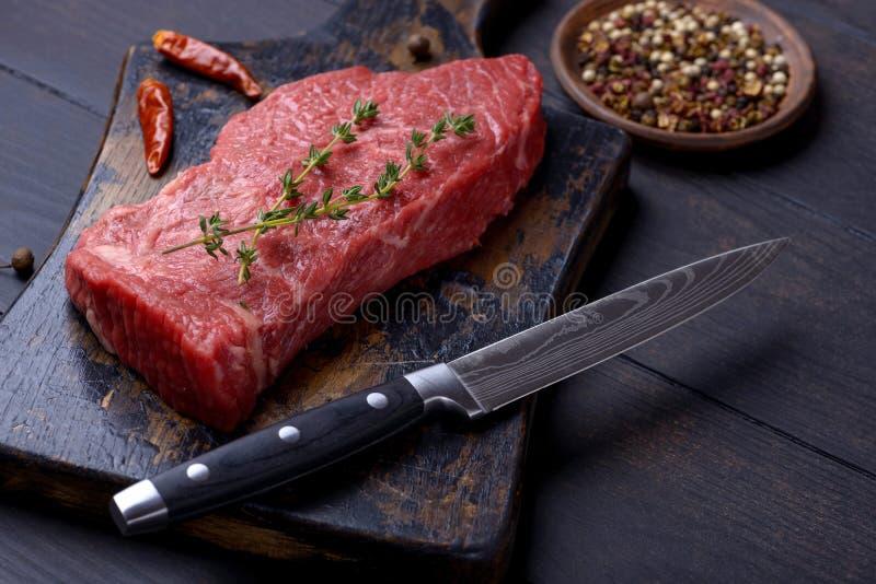 未加工的牛排用麝香草和胡椒和刀子 库存图片