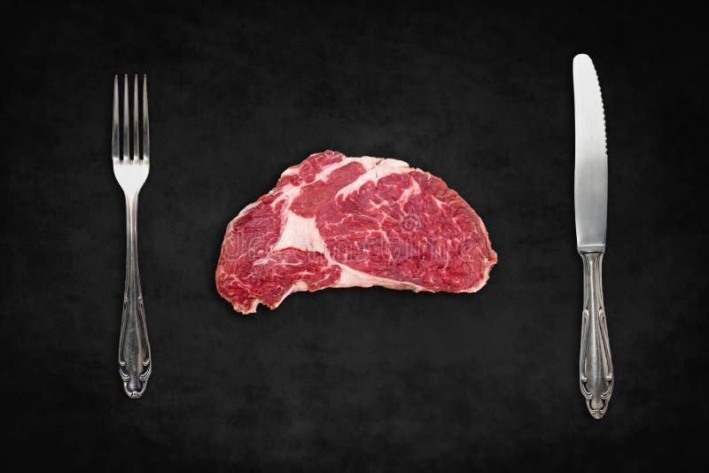 未加工的牛排/红肉与刀子和叉子在黑背景 库存图片
