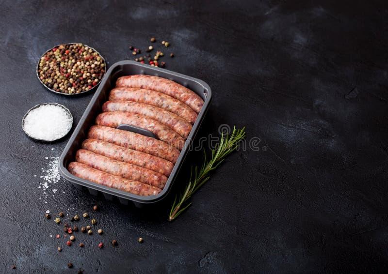 未加工的牛肉和猪肉香肠在塑料盘子有葡萄酒叉子的在黑背景 盐和胡椒 库存照片