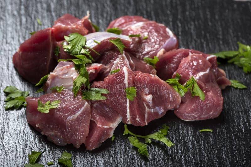 未加工的牛肉肉片断在黑暗的板岩的用绿色草本 库存图片
