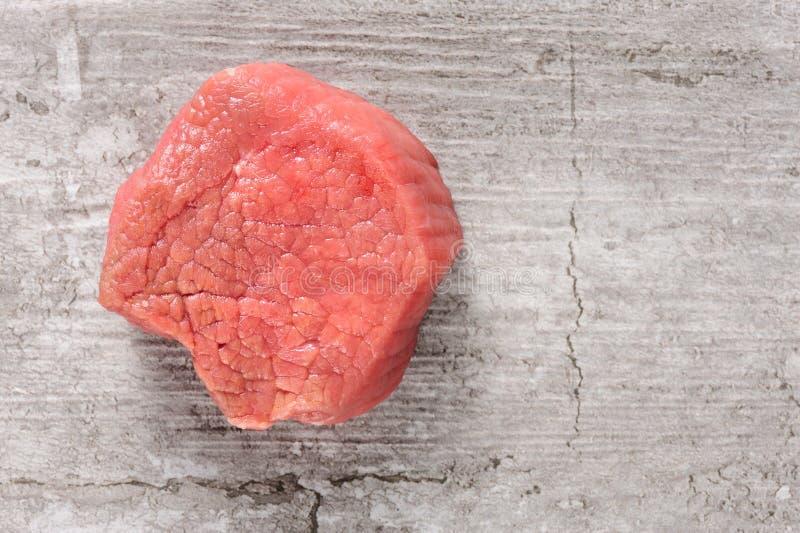 未加工的牛肉肉片断在破裂的石头或具体背景的 免版税库存图片