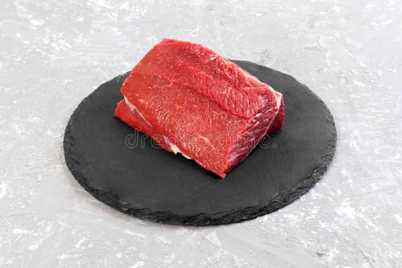 未加工的牛肉肉:新鲜的在板岩石头板材的牛肉猪肉大内圆角 免版税图库摄影