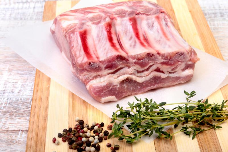 未加工的猪排、香料和迷迭香在切板 为烹调准备 库存图片