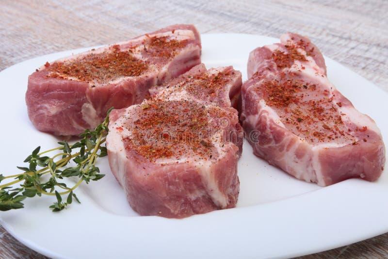 未加工的猪排、香料和迷迭香在切板 为烹调准备 免版税库存照片