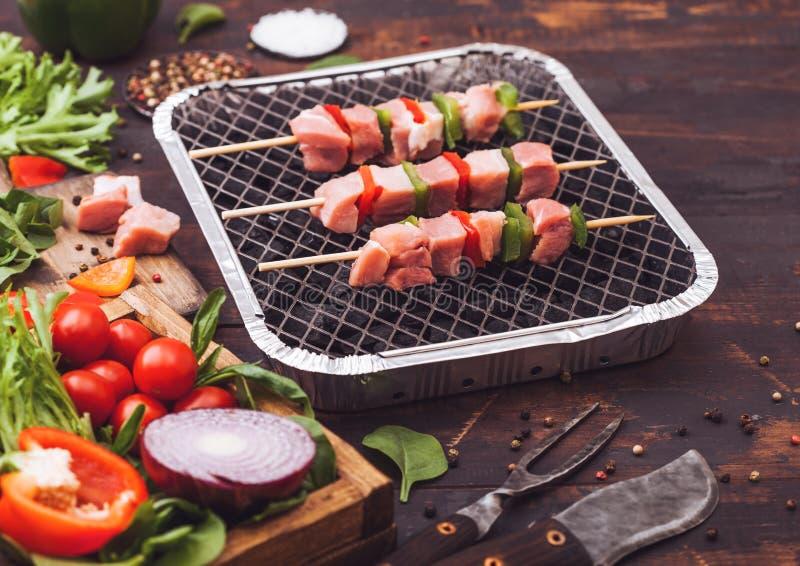 未加工的猪肉kebab用在一次性煤炭bbq格栅的辣椒粉与在木背景的新鲜蔬菜与叉子和刀子 ?? 库存图片