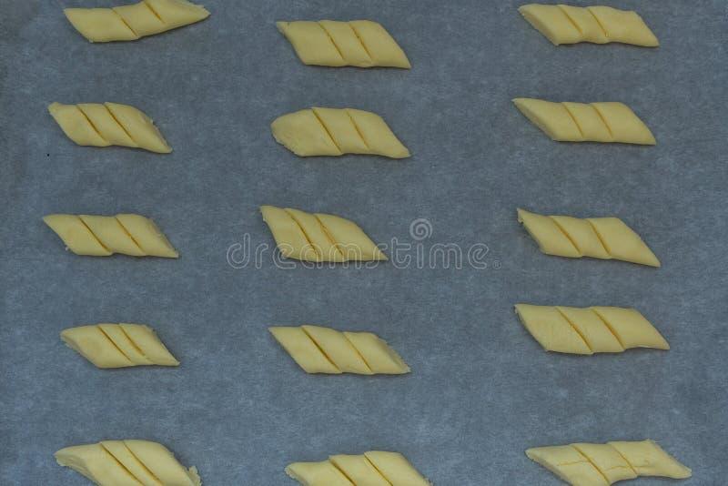 未加工的玉米淀粉曲奇饼的图象在蜡纸的在准备好一个烘烤的盘子被烘烤 免版税图库摄影