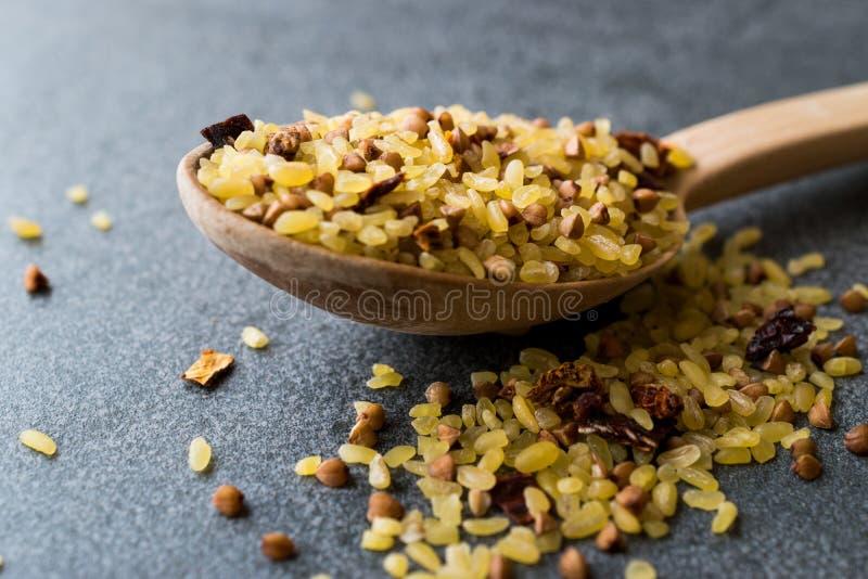未加工的碾碎干小麦米用在木匙子/Bulghur的荞麦Pilav或肉饭的 图库摄影