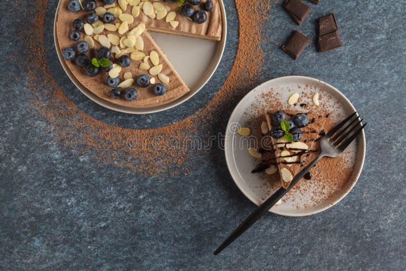 未加工的素食主义者巧克力焦糖乳酪蛋糕用蓝莓,未加工的罐头 免版税库存照片