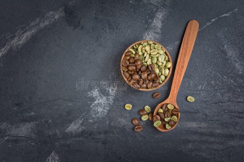 未加工的绿色和棕色烤咖啡豆顶视图在木碗和匙子的 免版税图库摄影
