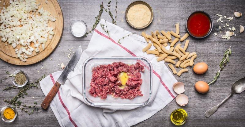 未加工的肉末球的准备与蛋面包渣的怂恿浆糊西红柿酱,大蒜草本调味料刀子切的葱 免版税库存图片
