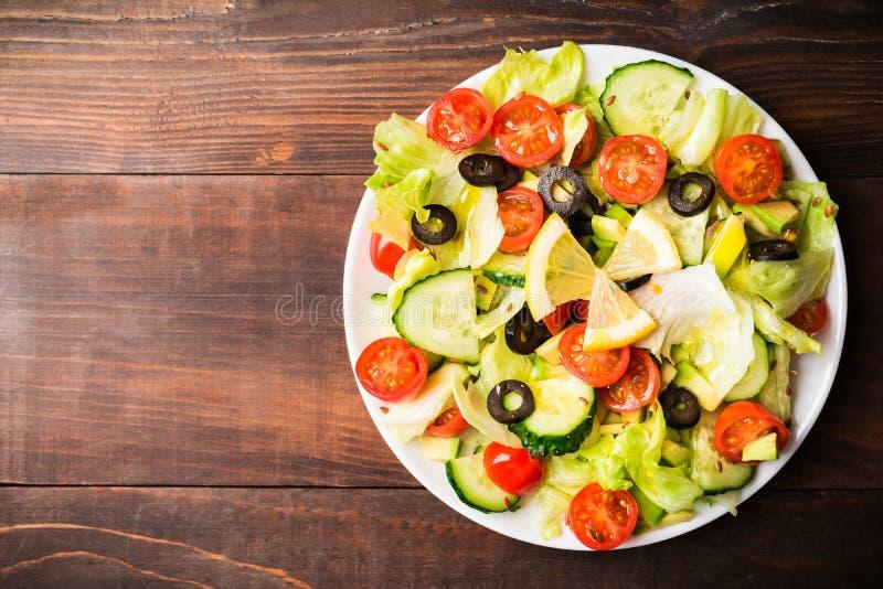 未加工的蔬菜沙拉用蕃茄、黄瓜、莴苣和鲕梨 免版税图库摄影