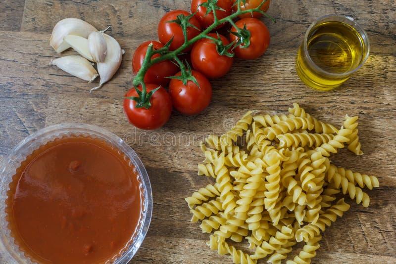 未加工的面团和成份面条,西红柿,橄榄油,大蒜为做传统意大利料理 库存照片