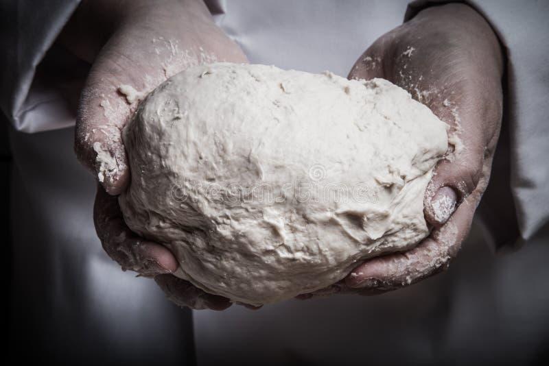 未加工的面团在厨师手上 定调子 图库摄影