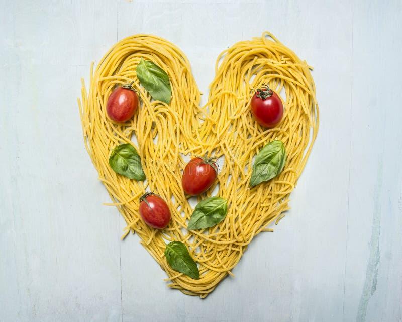 未加工的面团用西红柿和蓬蒿叶子被排行的心脏,在木土气背景顶视图关闭的情人节 免版税库存照片