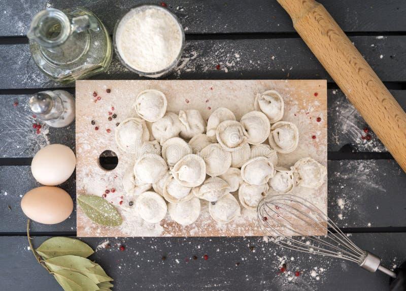 未加工的饺子,面粉,木板,花冠,瓶,油,香料,鸡蛋,月桂叶,滚针 免版税图库摄影