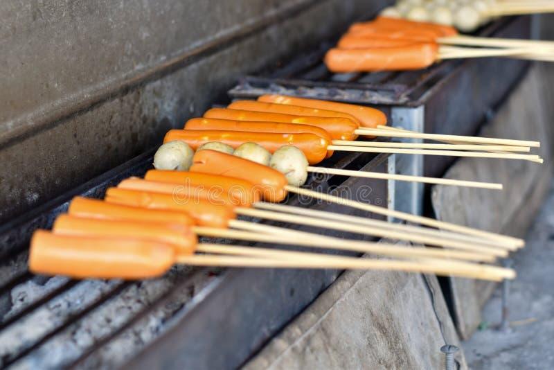 未加工的香肠烹调与热格栅 免版税库存图片