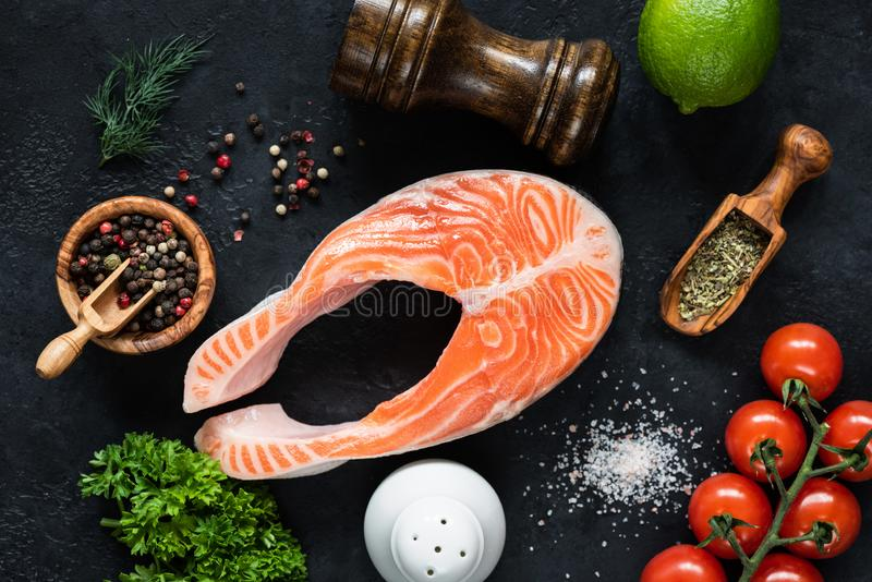未加工的鲑鱼排、菜和香料烹调的在黑板岩 库存照片