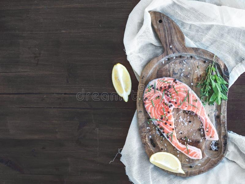 未加工的鲑鱼排用新鲜的草本、柠檬和香料在土气wo 免版税库存图片