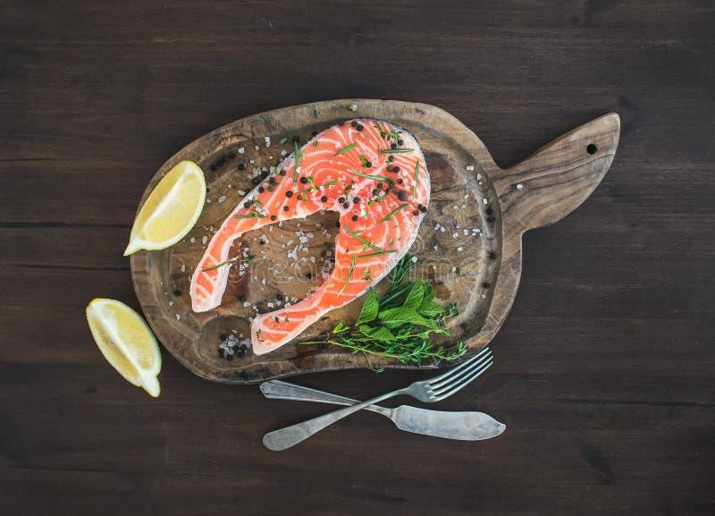 未加工的鲑鱼排用新鲜的草本、柠檬和香料 免版税库存图片