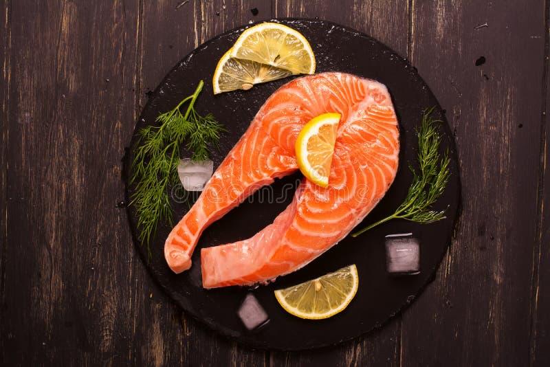 未加工的鲑鱼排用柠檬和草本 免版税库存照片