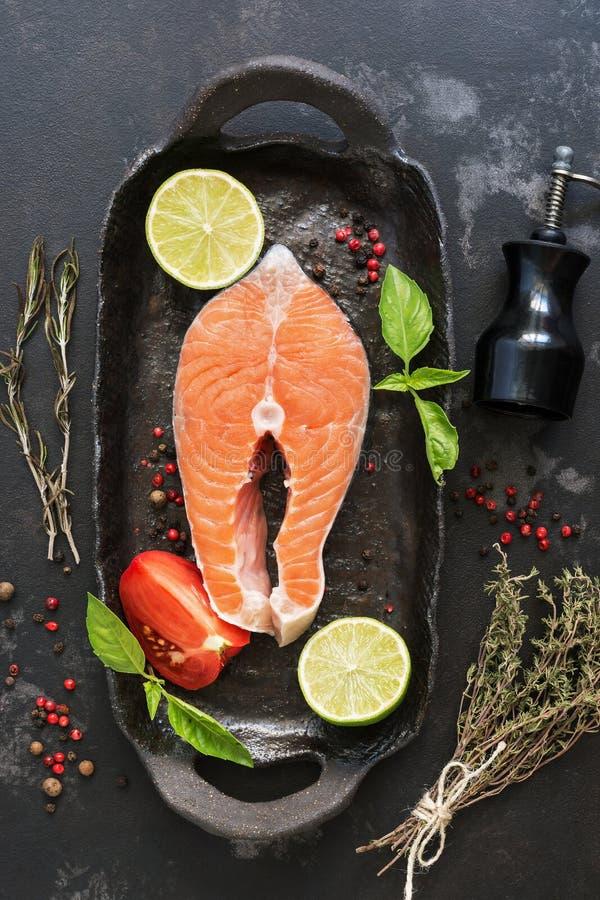 未加工的鲑鱼排用香料和草本在一个土气煎锅,黑石背景 顶视图,平的位置 库存图片