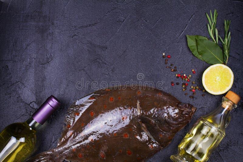 未加工的鲜鱼、白葡萄酒瓶、柠檬和草本在灰色石纹理背景 看法从上面,顶面演播室射击 库存照片