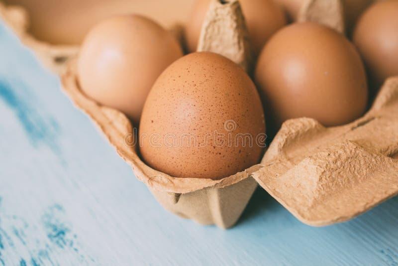 未加工的鸡鸡蛋接近的看法在蛋盒的在白色木背景 免版税库存图片