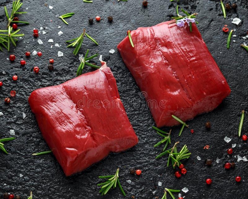 未加工的鹿肉牛排用迷迭香和胡椒在黑土气桌上 免版税库存照片