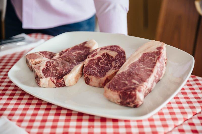 未加工的wagyu牛肉裁减从左到右:丁骨牛排、肋骨眼睛和无骨的顶面腰部牛排 免版税库存图片