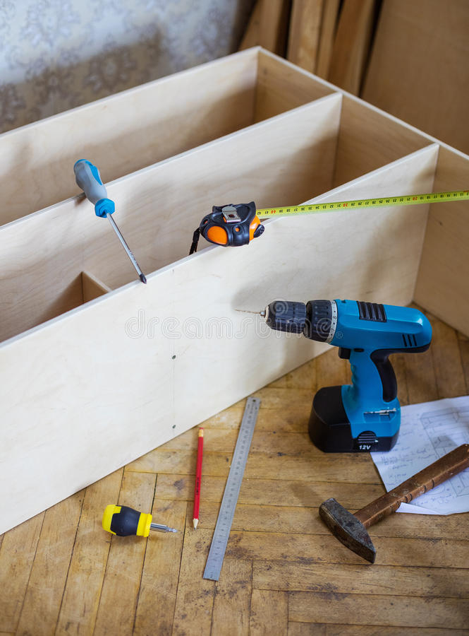 未完成的架子单位和工具在地板上在国内屋子里 免版税库存图片