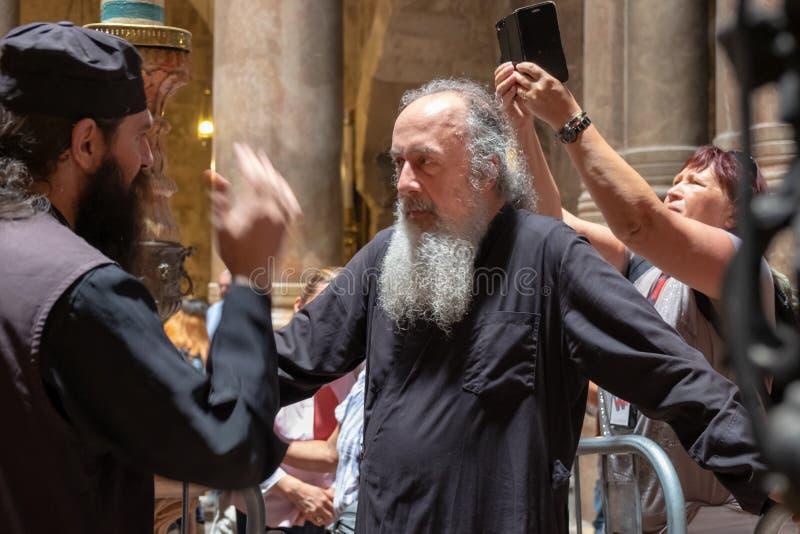 未定义的教士在耶路撒冷的圣墓教堂,耶稣基督的在十字架上钉死、埋葬和复活的站点 免版税库存照片