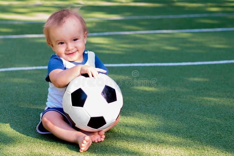 未来橄榄球明星:有足球的微笑的婴儿 使用与球的橄榄球场的愉快的小男孩 库存图片