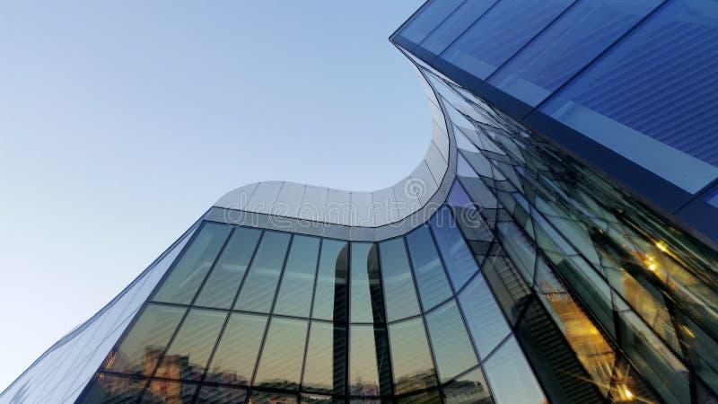 未来派弯曲的玻璃大厦,清楚的天空 免版税图库摄影