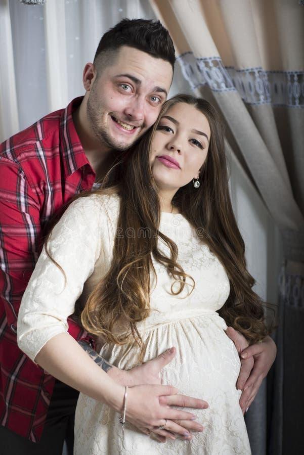 未来父亲轻轻地接触他怀孕的妻子的腹部 库存图片