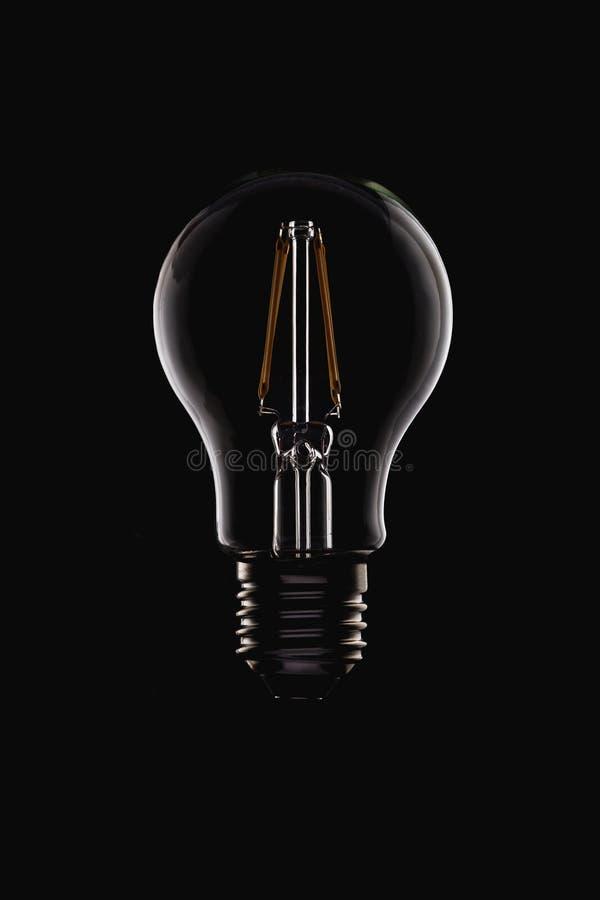 未点燃的在黑色的LED细丝圆的电灯泡 免版税库存图片