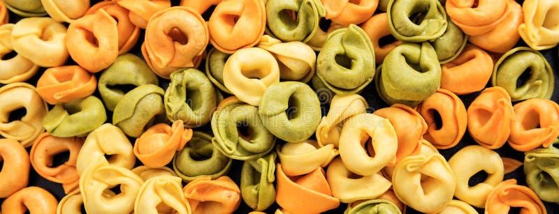 未煮过的五颜六色的意大利式饺子面团纹理背景,横幅 免版税库存照片