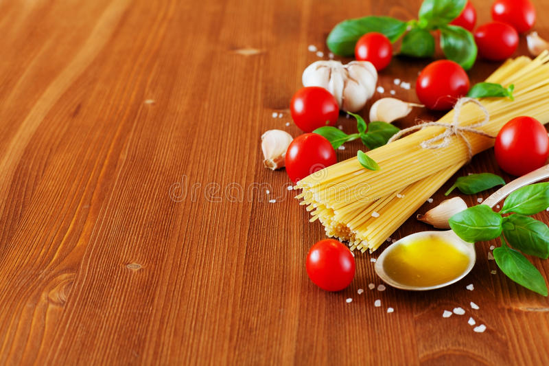 未煮过的意粉、西红柿、蓬蒿、大蒜和橄榄油,烹调的面团,食物背景成份 图库摄影