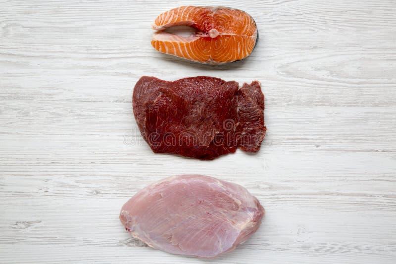 未煮过的未加工的鲑鱼排、牛肉肉和火鸡胸脯在白色木背景,顶视图 平的位置 图库摄影