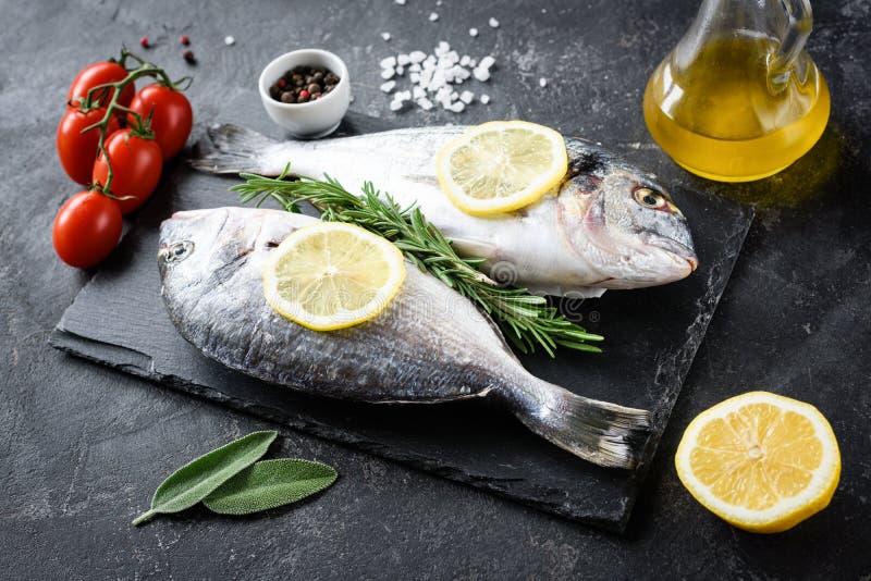 未煮过的海鲷鱼、橄榄油、柠檬和香料在板岩 免版税库存照片