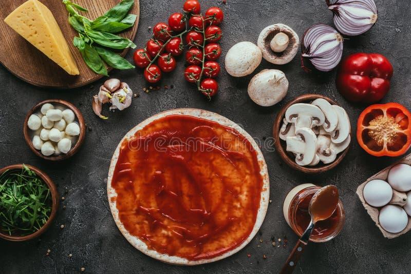 未煮过的薄饼面团顶视图用调味汁和菜 库存图片
