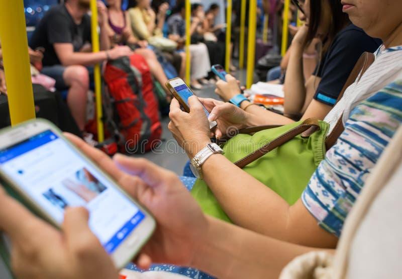 未知的人民乘地铁时使用手机,当旅行 图库摄影