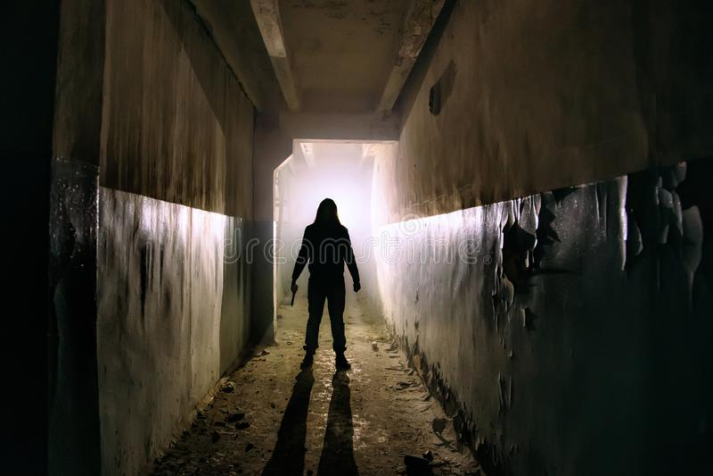 未知的人蠕动的剪影有刀子的在黑暗的被放弃的大厦 关于疯狂概念的恐怖 免版税库存图片