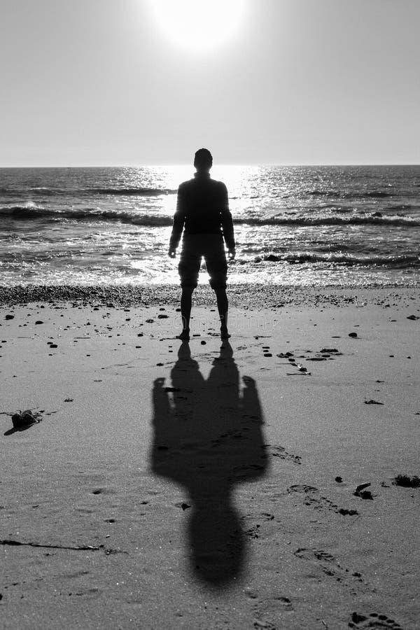 未知的人身分剪影在黑白的海滩的 寂寞和孑然概念 人在海背景现出轮廓 免版税库存照片