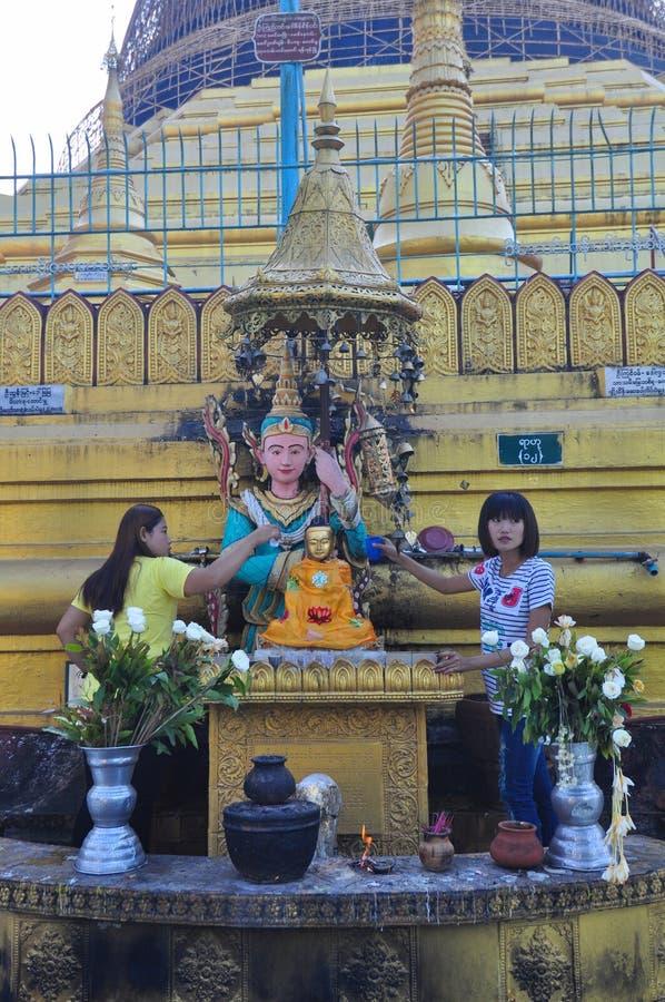 未知的游人倾吐水对菩萨雕象在Shwe M寺庙  图库摄影