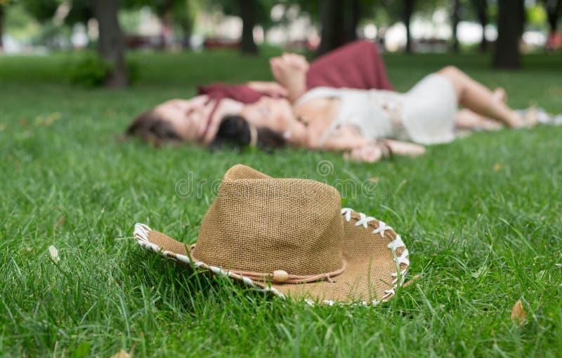 未聚焦的女孩在夏天公园,年轻嬉皮朋友leisu放松 免版税库存图片