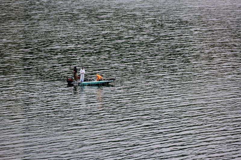 未认出的三个人钓鱼 免版税库存照片