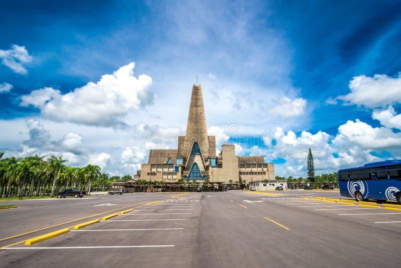 未认出的人和汽车在parkinkg在大教堂La Altagracia教会前面在Higuey,多米尼加共和国 图库摄影