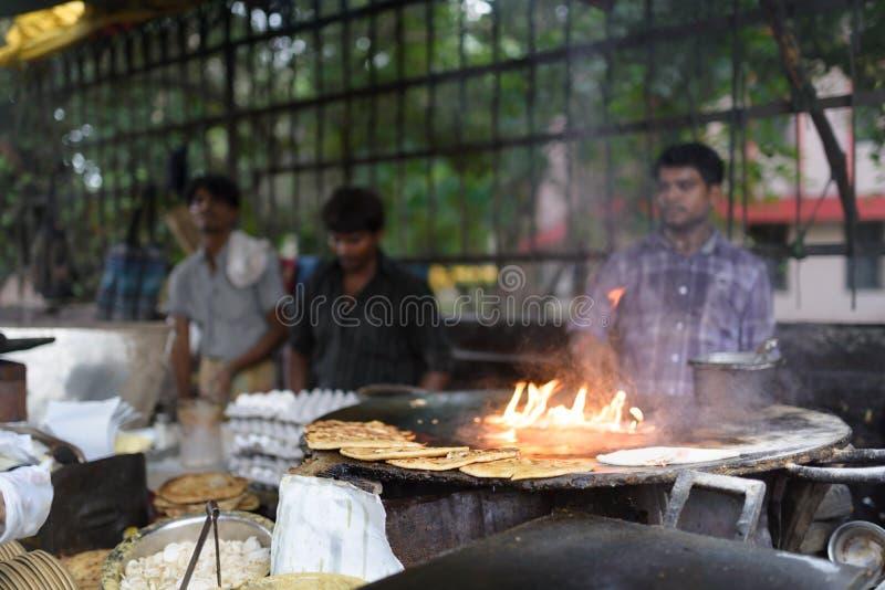 未认出的人在市场上的烹调印地安平的面包 库存照片